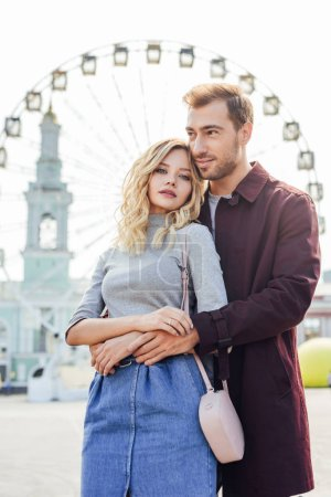young couple in autumn outfit hugging with observation wheel on background