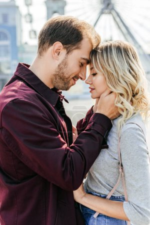 side view of affectionate couple in autumn outfit touching with foreheads in city