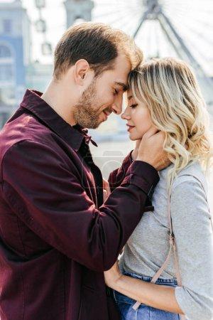 Photo pour Vue latérale d'un couple affectueux en tenue d'automne toucher avec les fronts en ville - image libre de droit