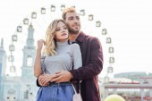 stylish couple in autumn outfit cuddling with observation wheel on background
