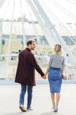 Photo for Back view of couple in autumn outfit holding hands and walking in amusement park - Royalty Free Image