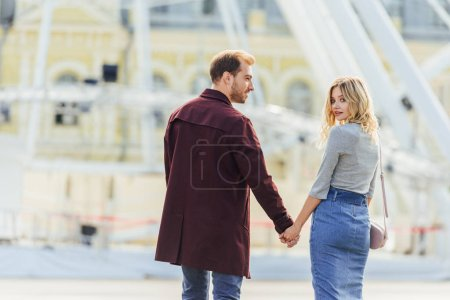 Photo for Rear view of couple in autumn outfit holding hands and walking in city - Royalty Free Image
