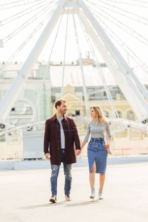 Photo for Couple in autumn outfit holding hands and walking near observation wheel - Royalty Free Image