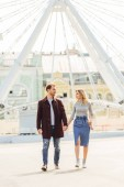 couple in autumn outfit holding hands and walking near observation wheel