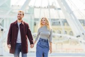 happy couple in autumn outfit holding hands and walking near observation wheel