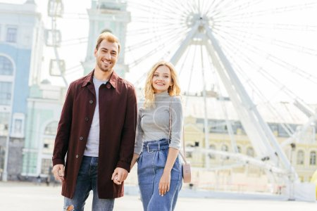 Photo for Happy couple in autumn outfit holding hands and standing near observation wheel - Royalty Free Image