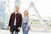 happy couple in autumn outfit holding hands and standing near observation wheel
