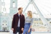 couple in autumn outfit holding hands and looking at each other near observation wheel