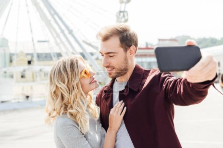 Photo pour Couple souriant en tenue d'automne en regardant l'autre et prenant selfie smartphone en ville - image libre de droit