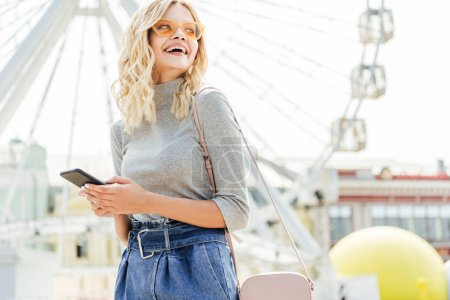 laughing beautiful woman in autumn outfit holding smartphone and looking away near observation wheel