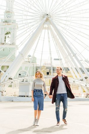 Photo for Romantic couple in autumn outfit holding hands and walking near observation wheel - Royalty Free Image