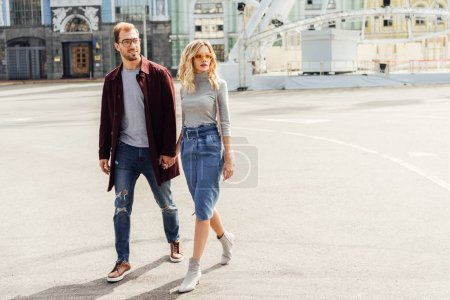 Photo for Stylish couple in autumn outfit holding hands and walking together in city - Royalty Free Image