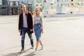 couple élégant en tenue d'automne tenant par la main et de marcher ensemble dans la ville