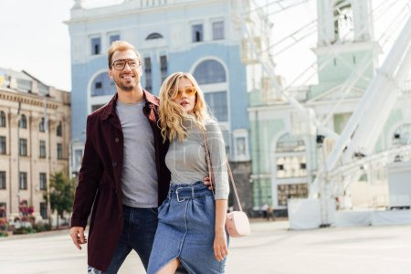 Photo for Romantic couple in autumn outfit hugging and walking in city - Royalty Free Image
