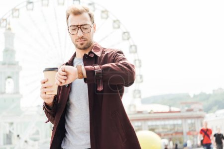low angle view of handsome man in autumn outfit holding coffee in paper cup and checking time near observation wheel
