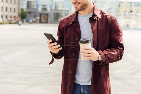 cropped image of man in autumn outfit holding coffee to go and using smartphone in city