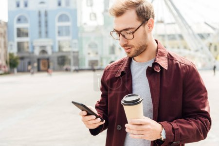 handsome man in autumn outfit holding coffee to go and using smartphone in city