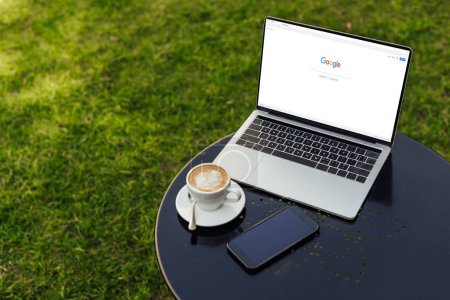 laptop with loaded google page, cup of coffee and smartphone on table in garden