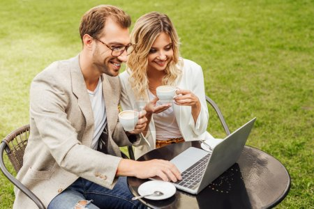 couple in autumn outfit working with laptop and drinking coffee in cafe