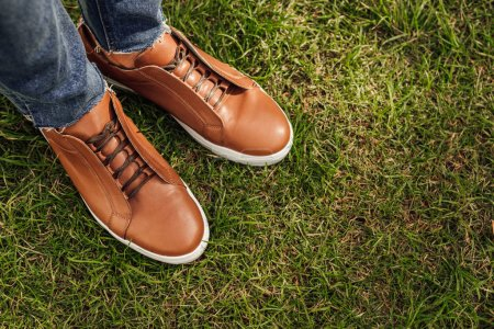cropped image of man in jeans and brown shoes standing on green grass in park