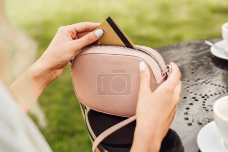 cropped image of woman taking credit card from handbag at table in cafe