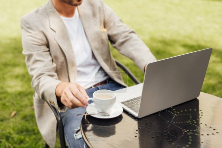 cropped image of freelancer in autumn outfit sitting at table with laptop and cup of coffee in garden