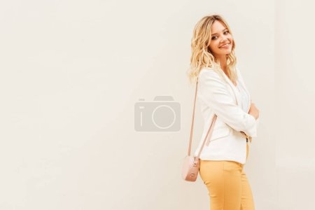 Photo for Smiling beautiful stylish woman in autumn outfit standing near beige wall in city and looking at camera - Royalty Free Image