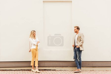 Photo for Couple in autumn outfit standing near beige wall on street and looking at each other - Royalty Free Image