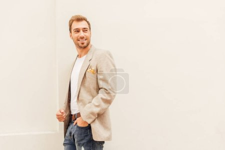 smiling handsome man in jacket and jeans standing near beige wall in city