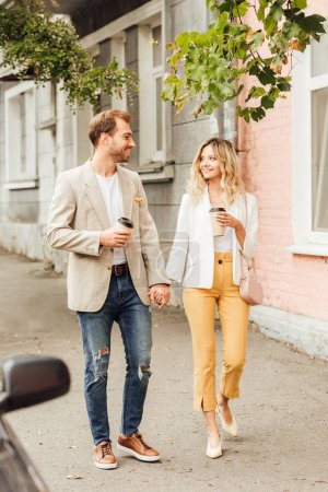 cheerful couple in autumn outfit holding hands, looking at each other and walking on street with disposable coffee cups