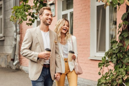 laughing couple in autumn outfit holding hands and walking on street with disposable coffee cups