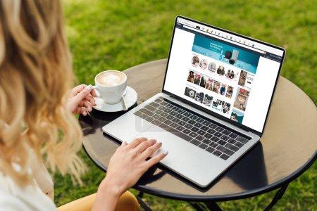 Photo pour Image recadrée de la femme en utilisant un ordinateur portable avec la page amazone chargée sur la table dans le jardin - image libre de droit