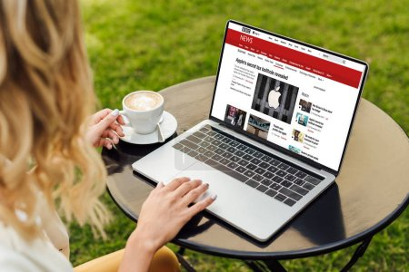 cropped image of woman using laptop with loaded bbc news page on table in garden