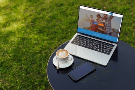 laptop with loaded couchsurfing page on table in garden
