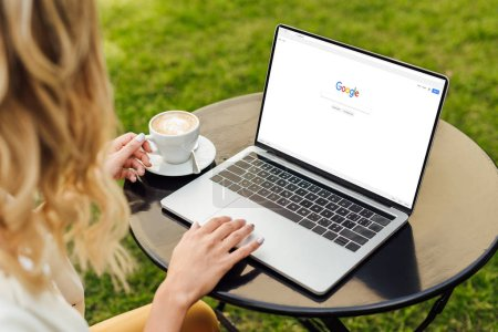 cropped image of woman using laptop with loaded google page on table in garden