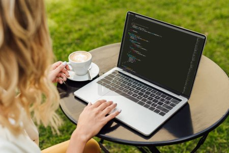 cropped image of woman using laptop with html code on table in garden