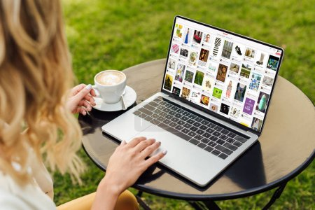 cropped image of woman using laptop with loaded pinterest page on table in garden