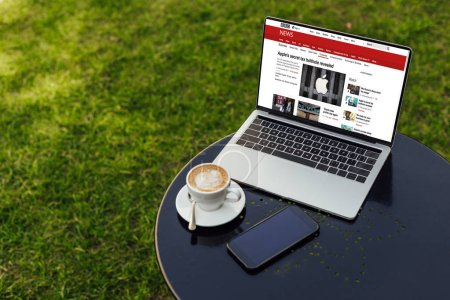 laptop with loaded bbc news page and smartphone on table in garden
