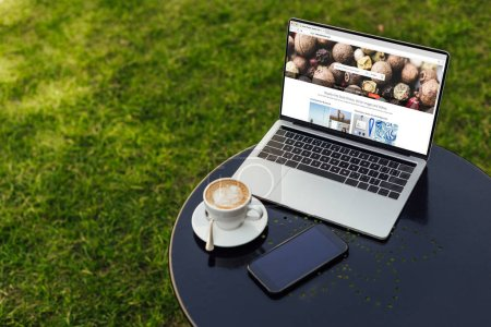 Photo for Laptop with loaded depositphotos page and smartphone on table in garden - Royalty Free Image