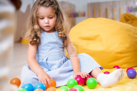 adorable kid sitting on carpet and looking at colorful balls in kindergarten