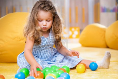 Photo for Adorable caucasian child sitting on carpet and playing with colorful balls in kindergarten - Royalty Free Image
