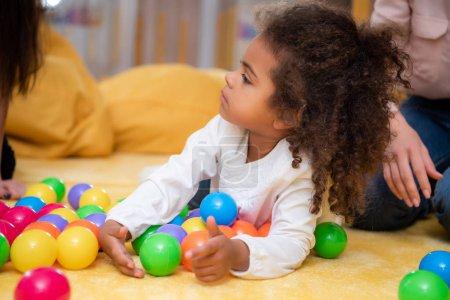 adorable african american kid lying on carpet with balls in kindergarten