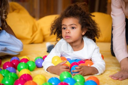 adorable african american kid lying on carpet with toys in kindergarten and looking away