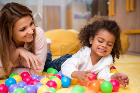 happy multicultural educator and kid playing with colored balls on carpet in kindergarten