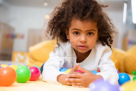 adorable african american kid lying on carpet with toys in kindergarten and looking at camera