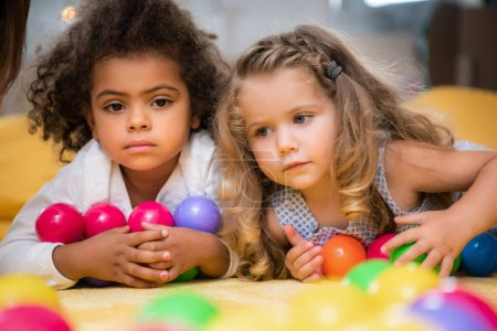 Photo for Adorable multicultural kids lying with colorful balls in kindergarten - Royalty Free Image