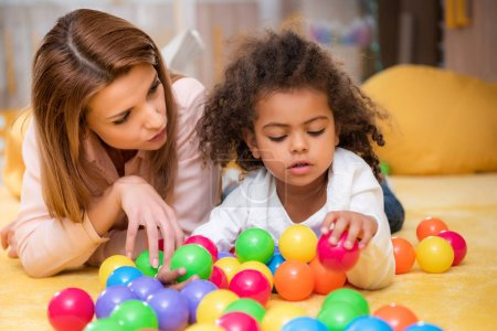 tutor and adorable african american child playing with colorful balls in kindergarten