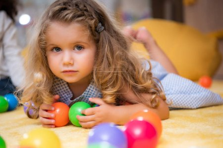 Photo for Adorable child lying on carpet with colorful balls in kindergarten and looking at camera - Royalty Free Image