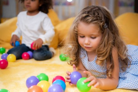 Photo for Multicultural kids playing with colorful balls on carpet in kindergarten - Royalty Free Image