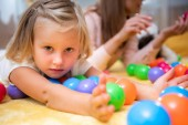 adorable child lying on floor with colored toys and looking at camera in kindergarten